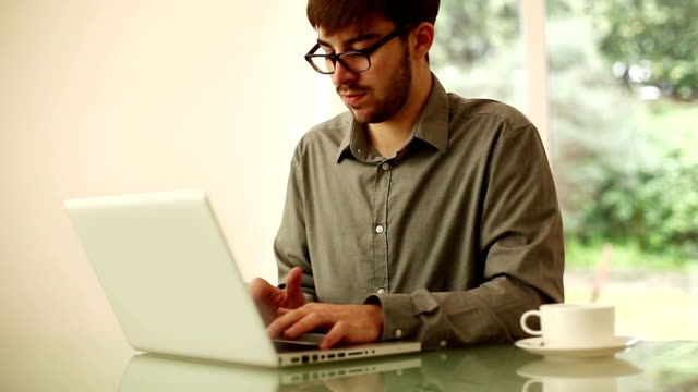 Young man typing on laptop, dolly shot. video