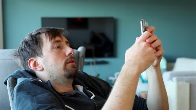 vídeos de stock, filmes e b-roll de jovem, escrevendo no smartphone em casa - sentando