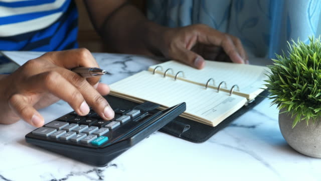 young man use calculator and writing on notepad at home office