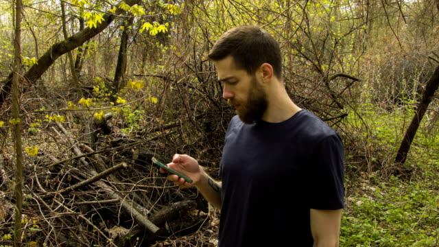 Young man uses a smartphone in a spring forest video