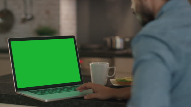 vídeos de stock e filmes b-roll de young man uses laptop with a green screen while sitting at the kitchen table. - modelo arte e artesanato