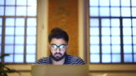 istock Young man using a laptop, reflection of a website in his glasses, close up 1186702063