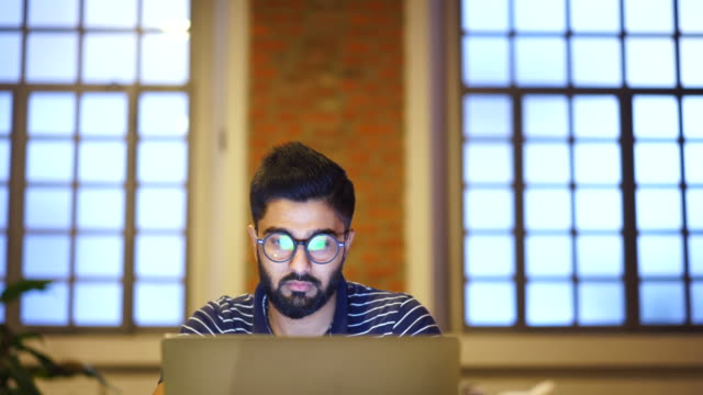 young man using a laptop, reflection of a website in his glasses, close up - studio camera video stock e b–roll