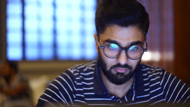 giovane che usa un laptop, riflesso di un sito web nei suoi occhiali, da vicino - curiosità video stock e b–roll