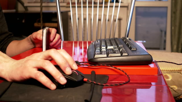 Young man using computer mouse sitting by the table at home video