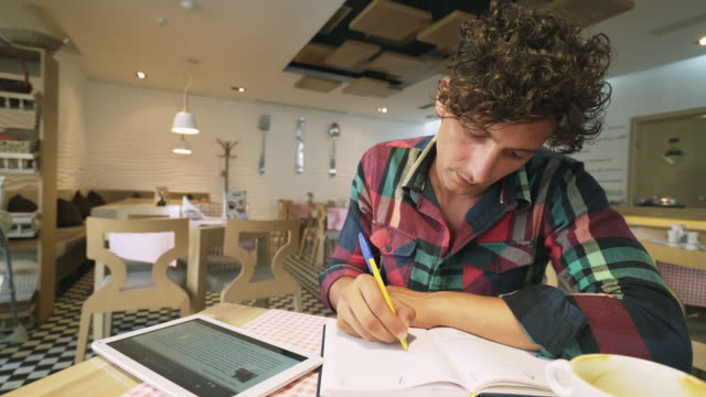 Young man using digital tablet and taking notes. video