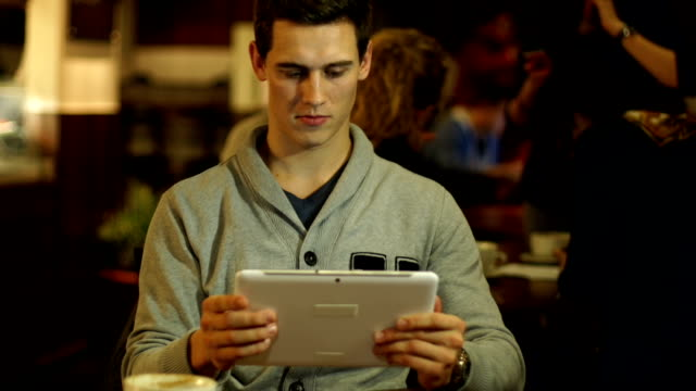 Young Man using Digital Tablet in Cafe / Coffee shop video