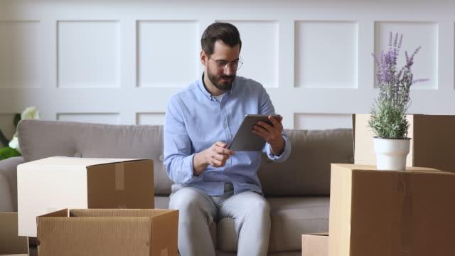 デジタルタブレットを使用する若い男は、ボックスとソファの上に座って - 荷物をとく点の映像素材/bロール