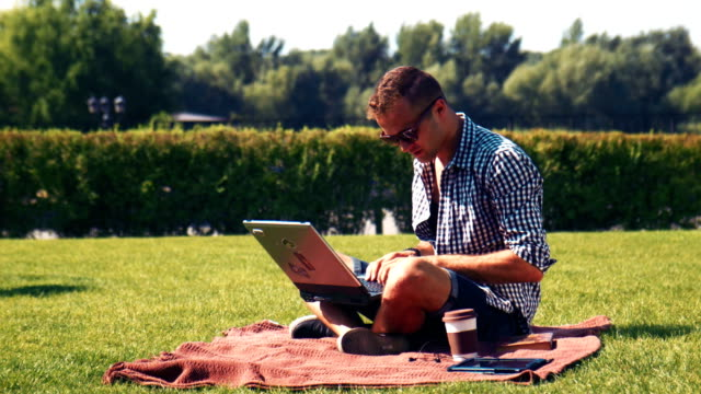 Young man using his laptop outdoors on the lawn video