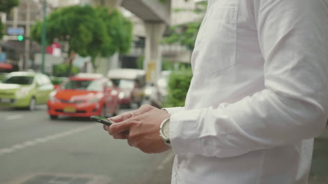 Young man using his smart phone in the city video