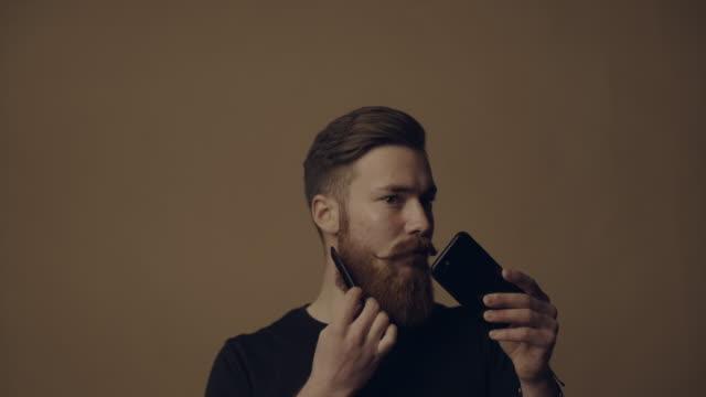 vídeos de stock, filmes e b-roll de jovem, usando seu tablet e smartphone, enquanto aparando e negligenciando sua barba - barba