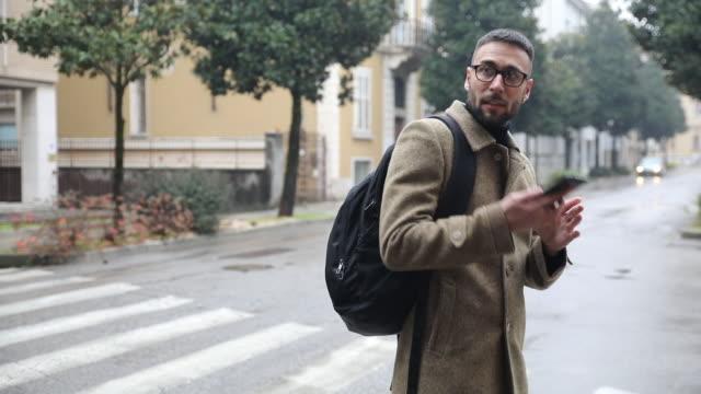 vidéos et rushes de jeune homme utilisant le téléphone portable pour appeler un taxi - vidéo stock - homme faire coucou voiture