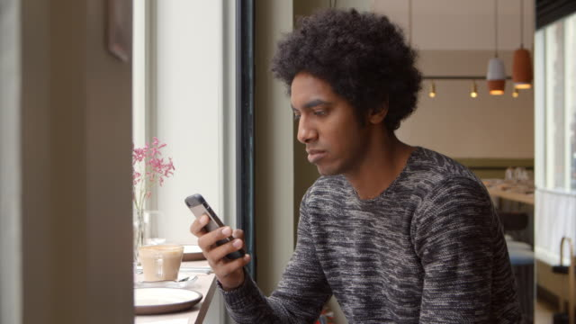 Young Man Using Mobile Phone To Update Social Media In Cafe video