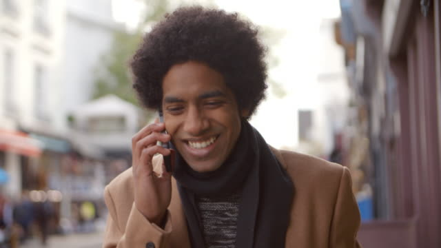 Young Man Using Phone As He Walks Along Busy City Street video