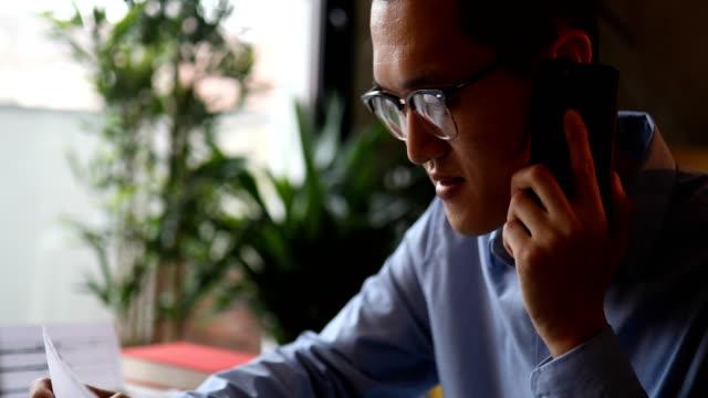 彼のオフィスで電話を使用して若い男 - 電話を使う点の映像素材/bロール