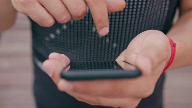 ung man använder telefonen utomhus - skrollning bildbanksvideor och videomaterial från bakom kulisserna