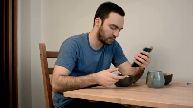 Young man using phone while eating breakfast video