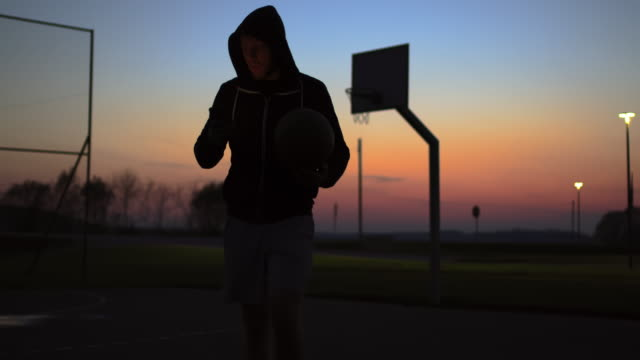 MS Young man using smart phone and walking off outdoor basketball court at dusk