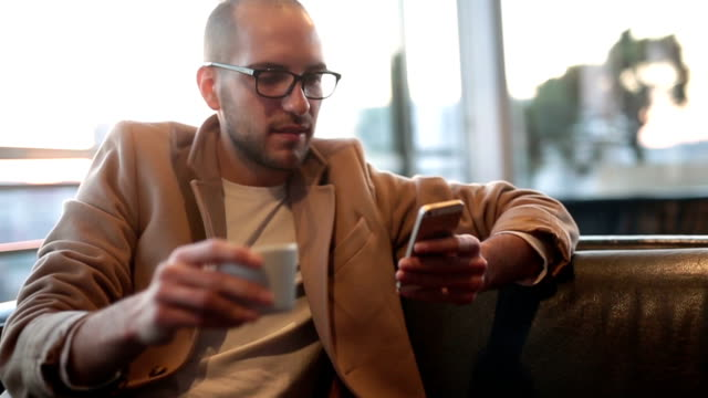 Young man using smart phone in coffee shop video