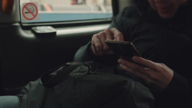 junger mann mit smartphone im auto. - instant messaging stock-videos und b-roll-filmmaterial