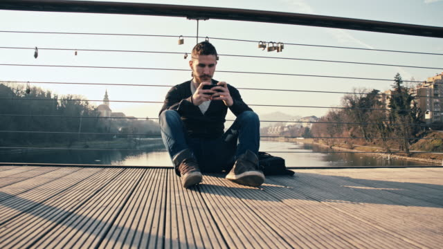 WS joven usando teléfono inteligente en el puente - vídeo