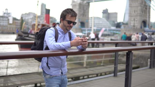 junger mann mit smartphone  - englandreise stock-videos und b-roll-filmmaterial