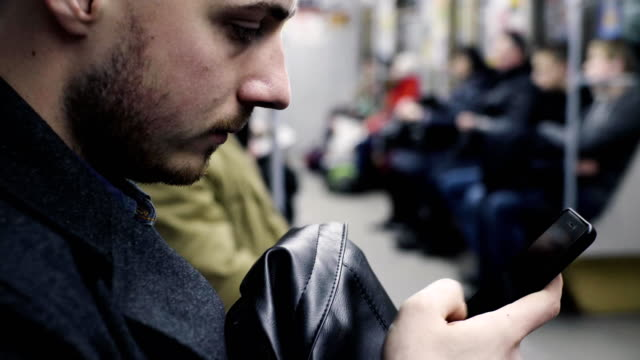 Young man using smartphone during metro ride Young man using smartphone during metro ride. underground stock videos & royalty-free footage