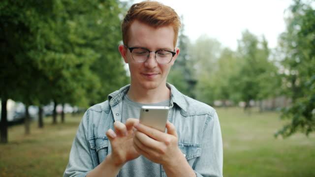 young man using smartphone in park touching screen enjoying modern device - solo un uomo giovane video stock e b–roll