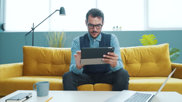 young man using tablet in a modern workplace. - {{asset.href}} video stock e b–roll