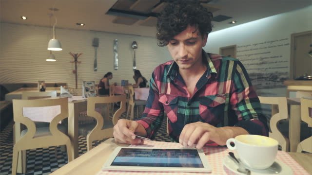 Young man using tablet pc and credit card inside coffee shop. Young man using tablet pc and credit card inside coffee shop. He is using the card for online shopping. credit card purchase stock videos & royalty-free footage