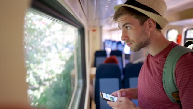 young man using the phone on the train - турист с рюкзаком стоковые видео и кадры b-roll