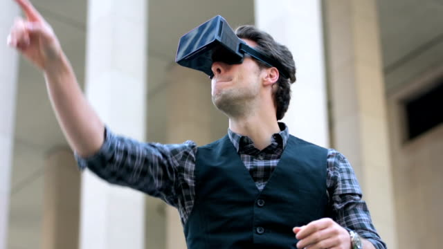 Young man using virtual reality outdoors video