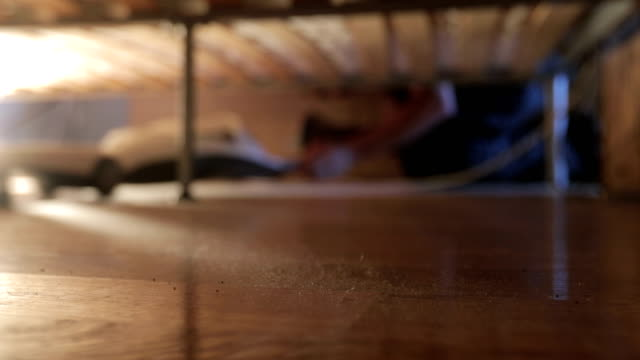 young man vacuum cleaning dust under his bed - sotto video stock e b–roll