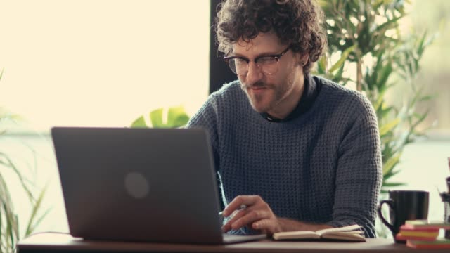 vídeos y material grabado en eventos de stock de hombre joven de chats de vídeo y tomar notas en la oficina en casa - trabajo freelance