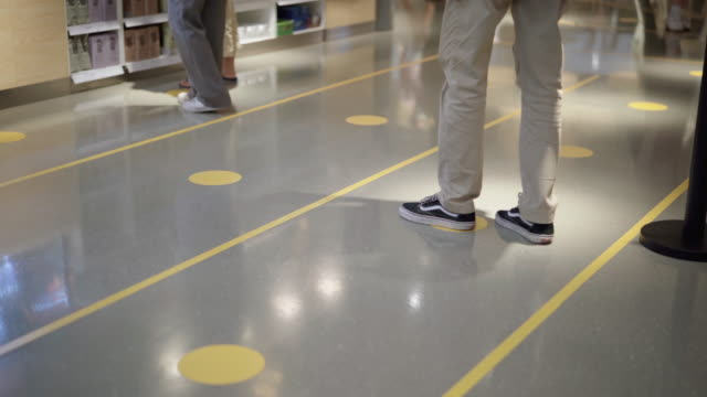 vidéos et rushes de jeune homme attendent leur tour dans une file d'attente pour accéder aux supermarchés et appliqué des règles de distanciation sociale - faire la queue