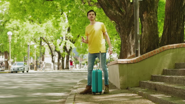 Ung man väntar på en taxi i staden video