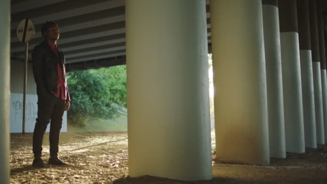 Young man waiting for someone under bridge.