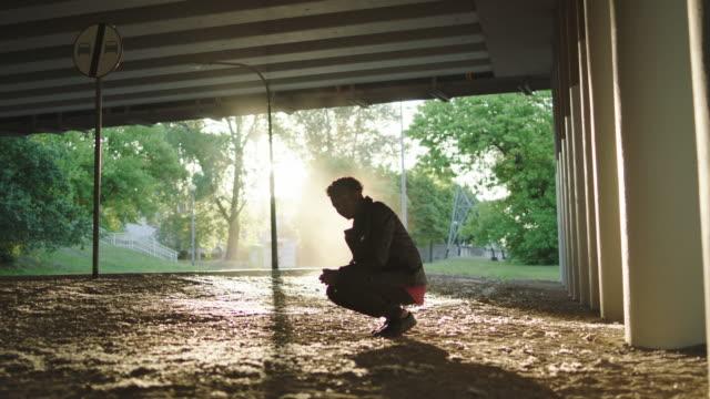 young man waiting for someone under bridge. - solo un uomo video stock e b–roll
