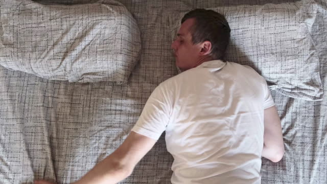 young man wakes up in the morning to an empty bed and looking for the hand of his girlfriend or wife, slow motion, top view - {{relatedsearchurl(carousel.phrase)}} video stock e b–roll