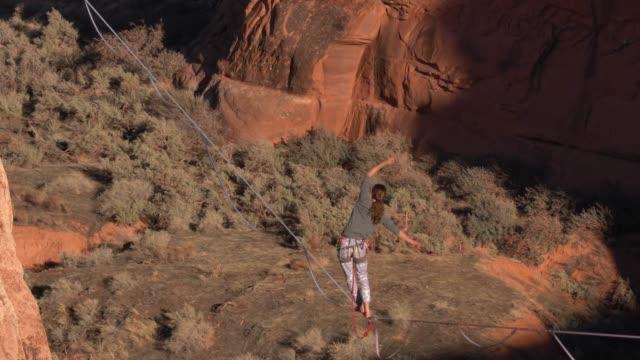 Young Man walking a slackline over a canyon near Moab, Utah video