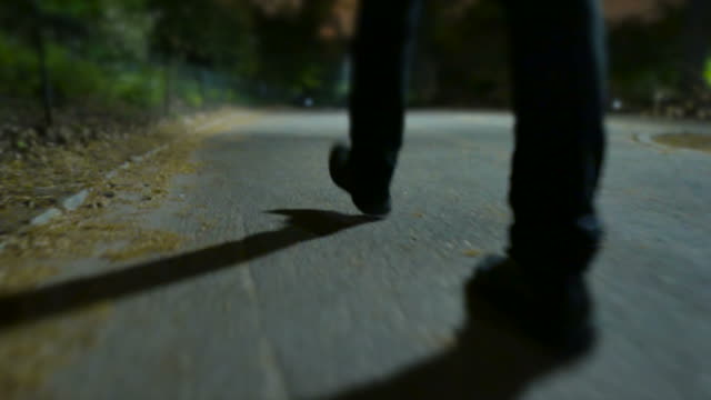 Young Man Walking in Spooky Scenery. Scary Atmosphere in a Park at Night. Close Up on Shoes. Shadows made by Street Lamps.