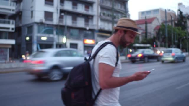vídeos de stock, filmes e b-roll de homem novo que anda na cidade usando o gps do smartphone - ática ática