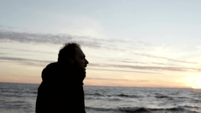 junger mann zu fuß am ufer des meeres allein und auf der suche auf den wellen. männlich, genießen den sonnenuntergang am strand - ostsee stock-videos und b-roll-filmmaterial