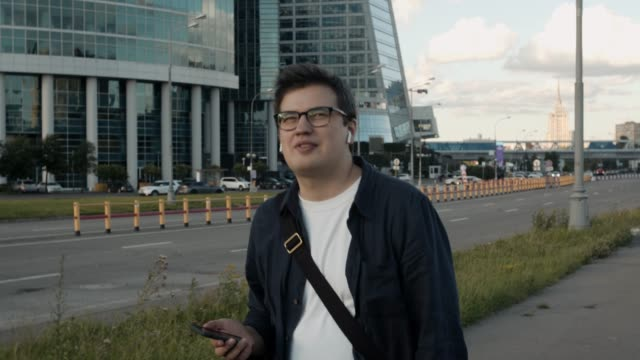 young man walking near moscow city buildings, talking on the phone - auricolari wireless video stock e b–roll