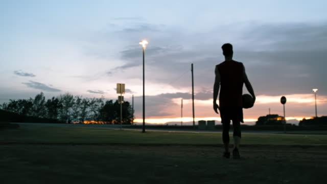 ms ung man går av utomhus basketplan i skymningen - basketboll boll bildbanksvideor och videomaterial från bakom kulisserna