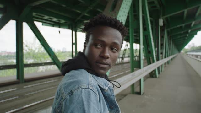 young man walking on roadtruck under bridge. loneliness - podążać za czynność ruchowa filmów i materiałów b-roll