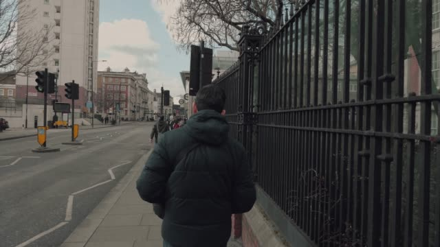 Young man walking on the street in witer Young man walking and snow falling in city. London, England tripping falling stock videos & royalty-free footage