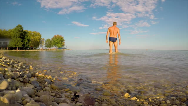Young man walking on the water in the beach in lake Balaton of Hungary in summertime Young man walking on the water in the beach in lake Balaton of Hungary in summertime hungary stock videos & royalty-free footage
