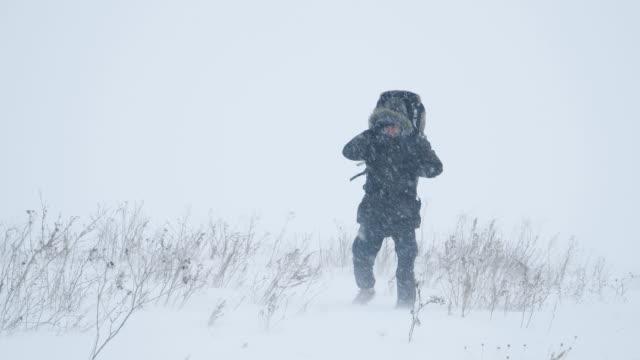 ung man vandrar genom en snöstorm - snöstorm bildbanksvideor och videomaterial från bakom kulisserna