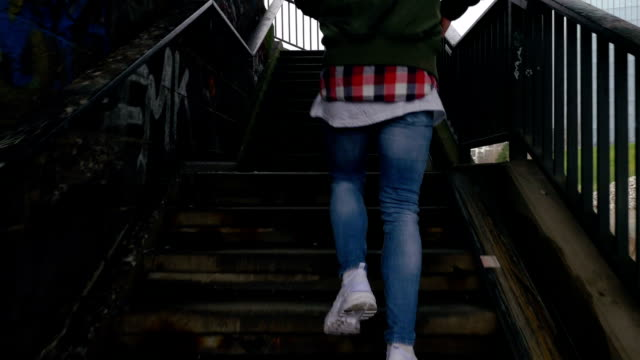 young man walking up outdoor staircase in frankfurt rear view - balaustrata video stock e b–roll